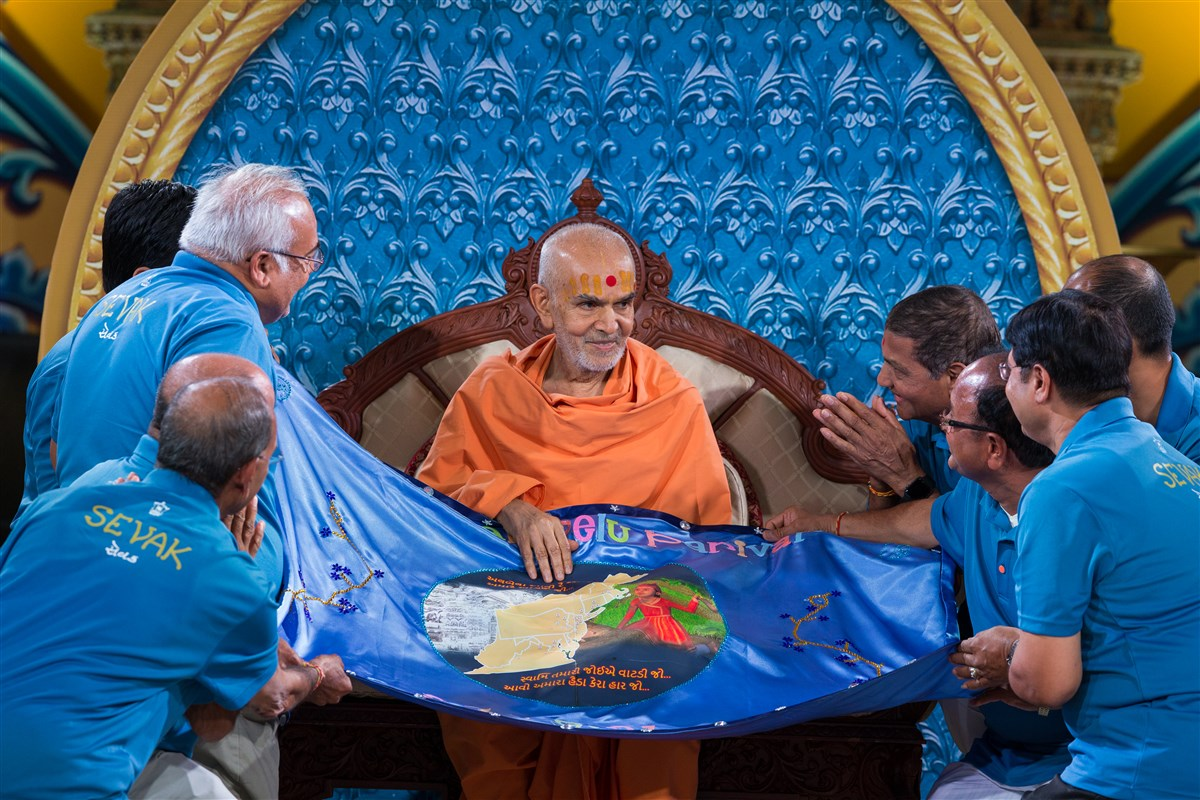Swamishri is offered a shawl by devotees, 19 August 2017