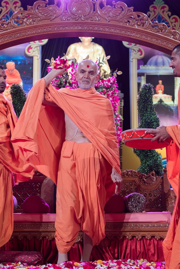 Swamishri showers the devotees in the audience with flowers, 19 August 2017