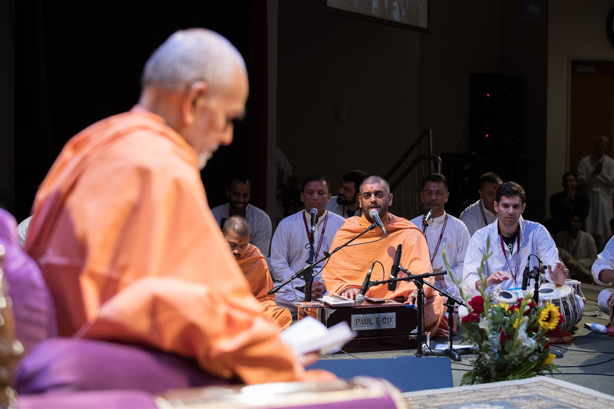 Swamis and devotees sing kirtans during Swamishri's puja
