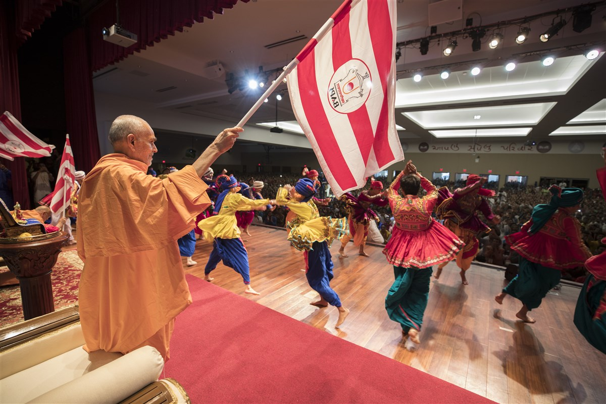 Swamishri waves the BAPS flag during the welcome dance