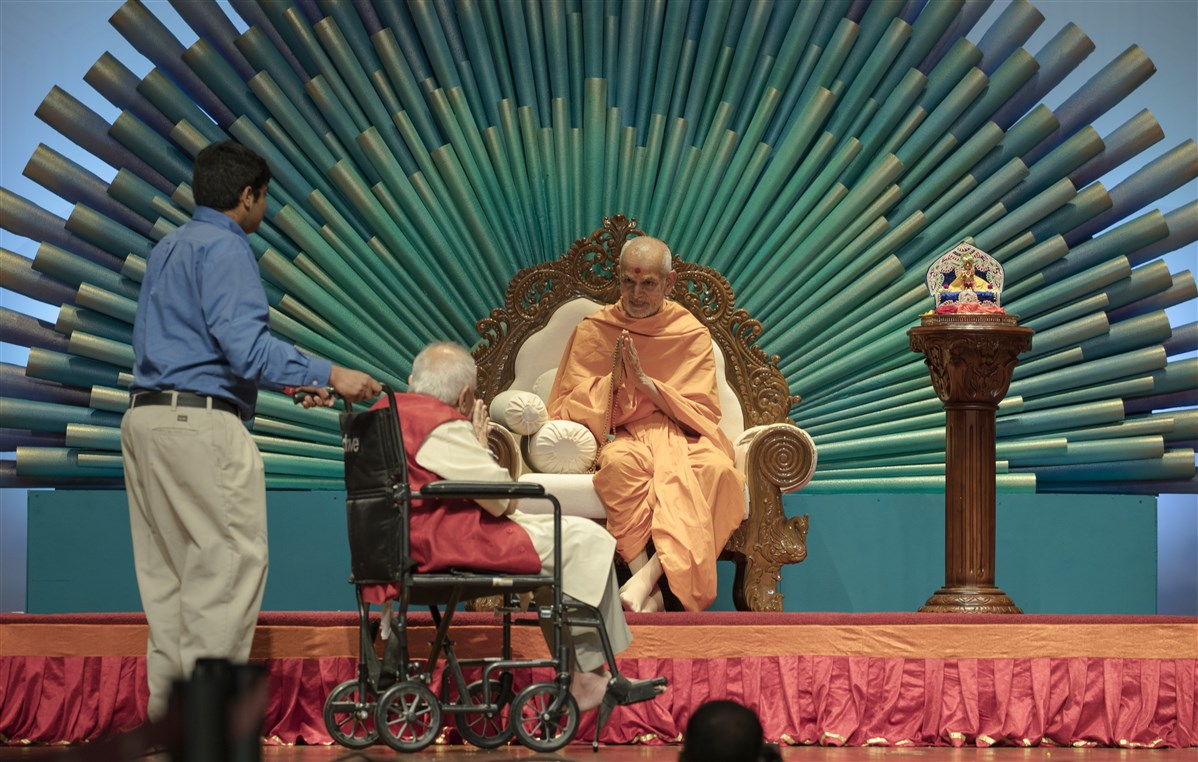 Swamishri greets a devotee with folded hands