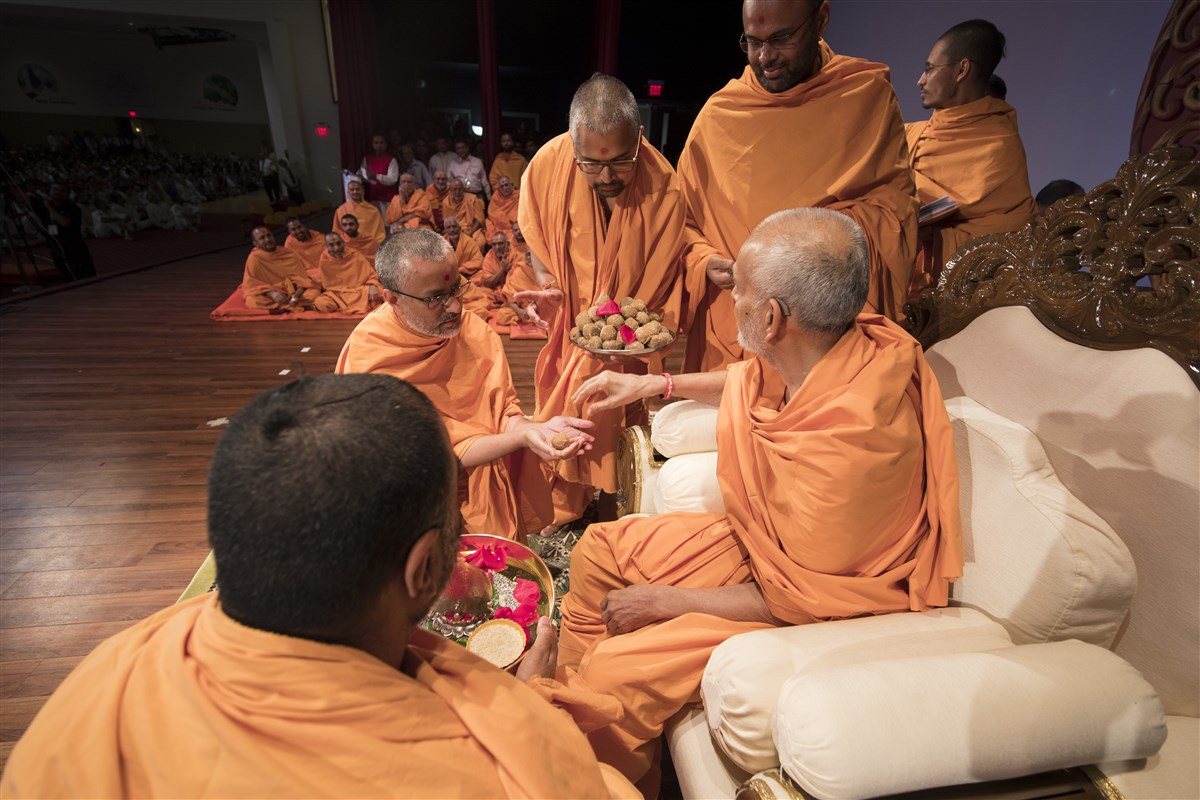 Swamishri gives prasad to swamis
