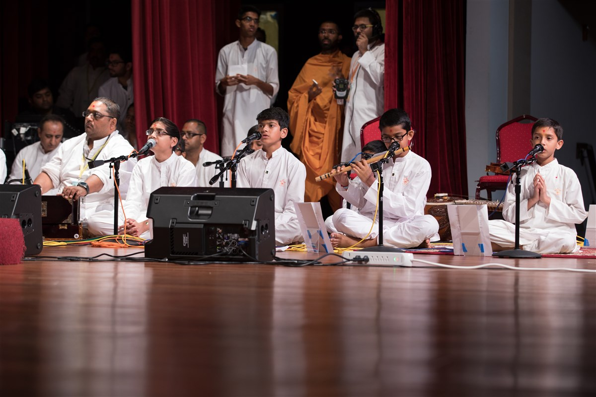Children sing kirtans during puja
