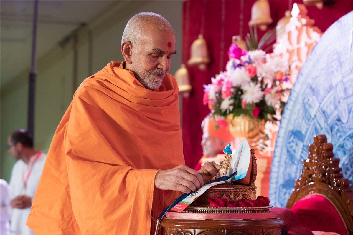 Swamishri puts an ID Badge for the North American Youth Convention 2018 on Shri Harikrishna Maharaj