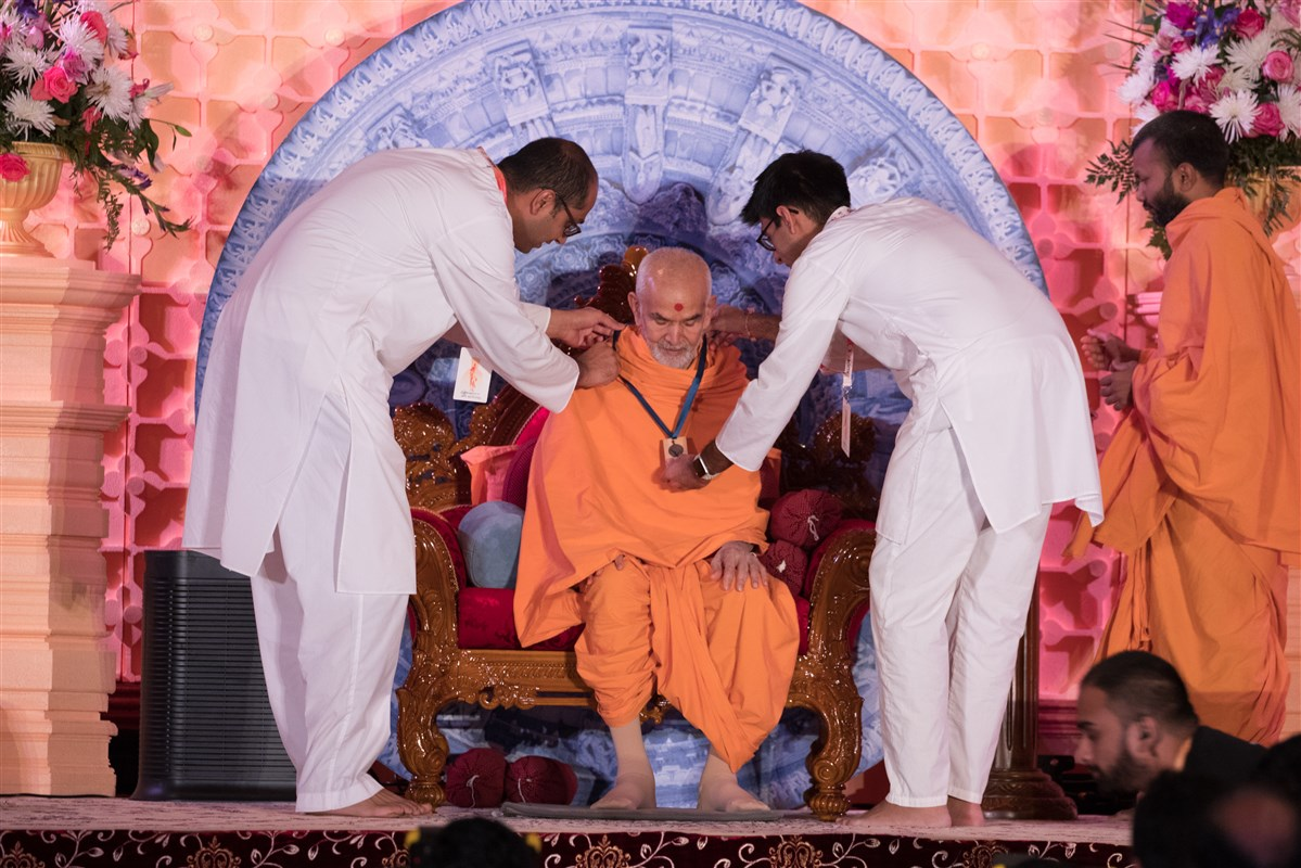 Youths put an ID Badge on Swamishri