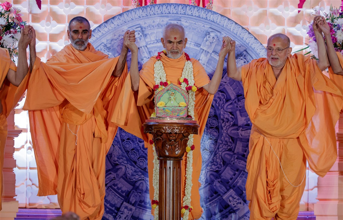 Swamishri joins hands with swamis in a gesture of unity