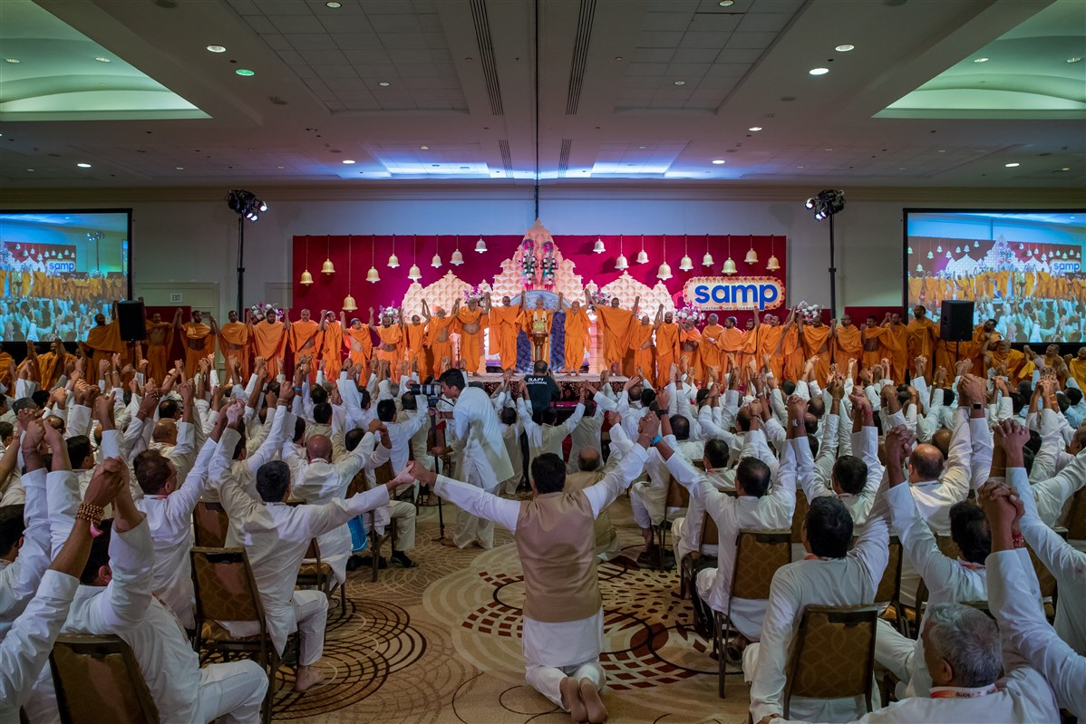 Swamishri joins hands with swamis and seminar delegates in a gesture of unity