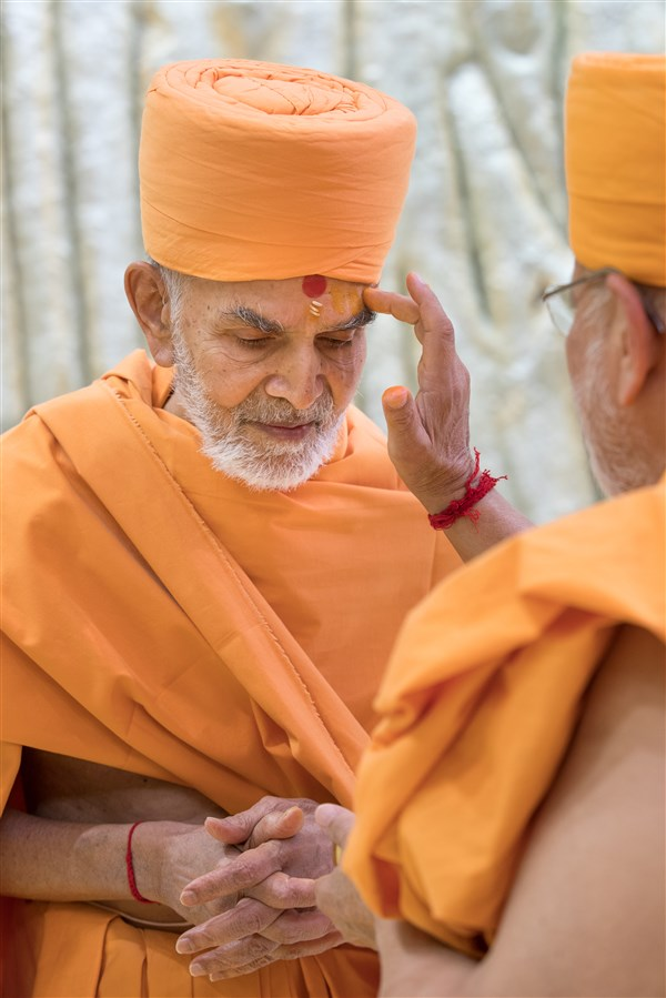 Pujya Ishwarcharandas Swami applies chandan to Swamishri