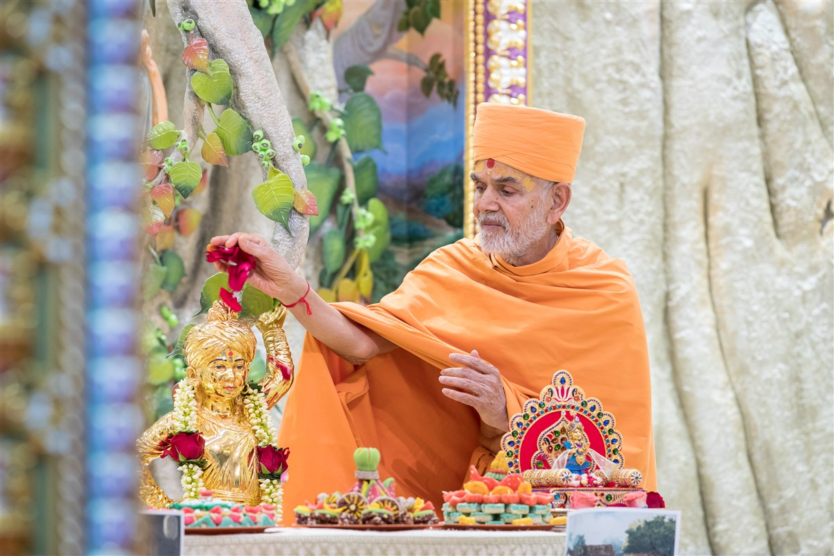 Swamishri showers flowers on Shri Ghanshyam Maharaj