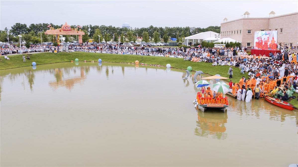 Swamishri rides a boat in the Brahmasarovar during the Jal Jhilani festival