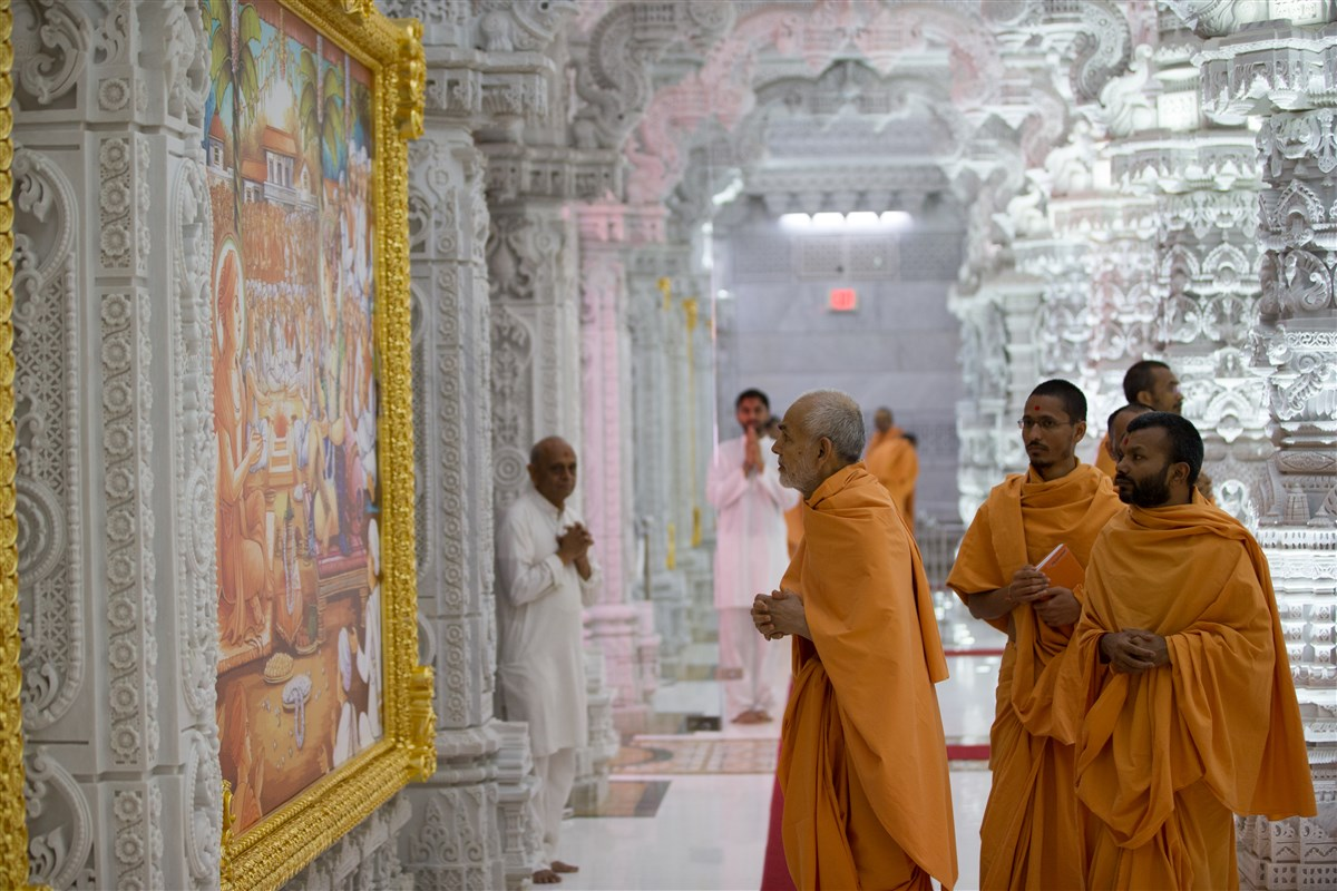 Swamishri observes murals around the mandir