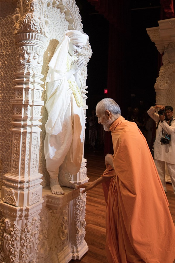 Swamishri touches the feet of a child playing the role of a paramhansa