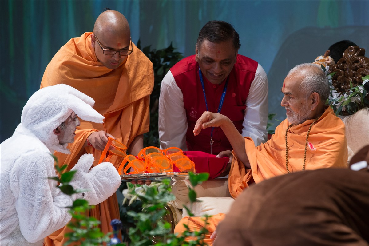Swamishri blesses glasses to demonstrate to the assembly to see divyabhav in all