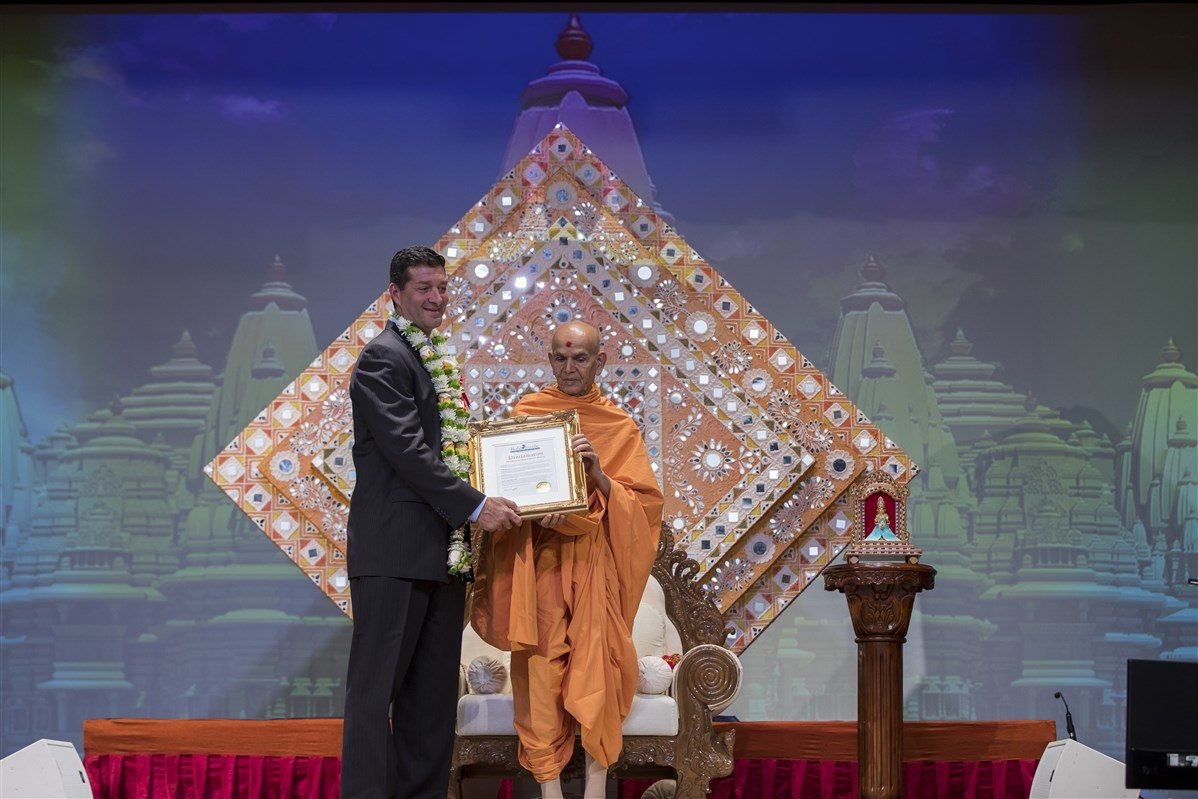 Mayor of Robbinsville David Fried presents a proclamation to Swamishri