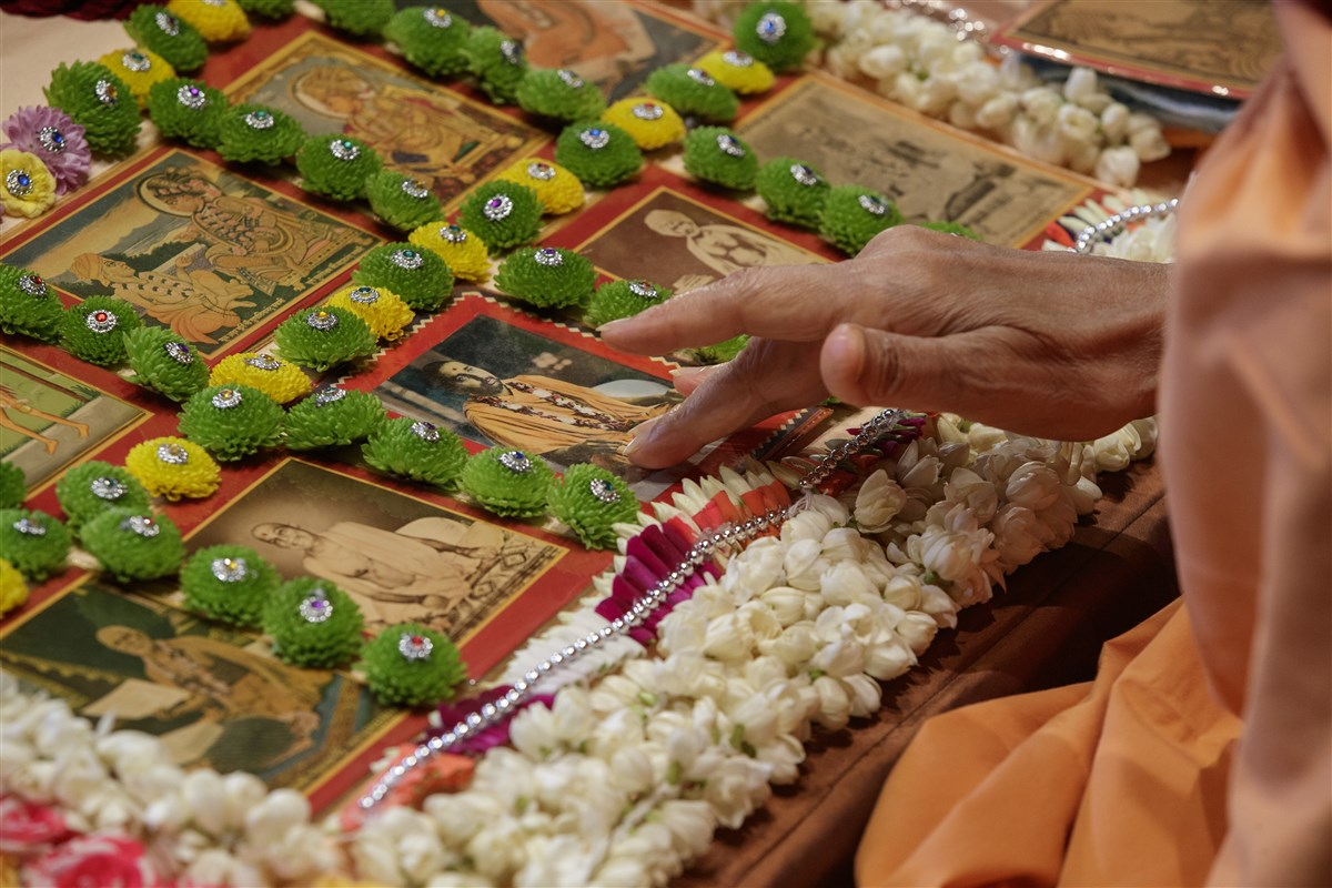 Swamishri touches the feet of the murtis in puja