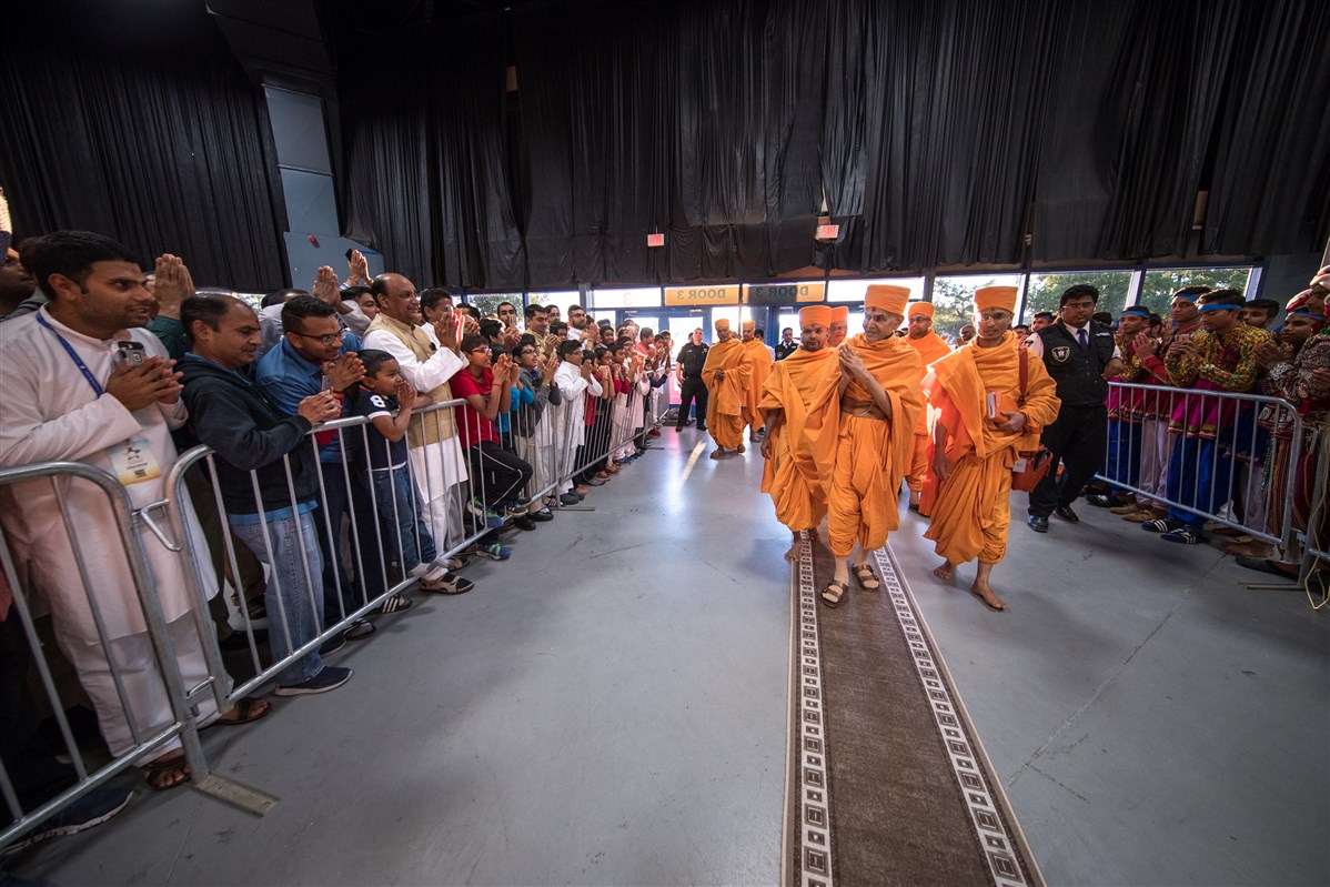 Swamishri greets devotees with folded hands as he arrives for the evening assembly