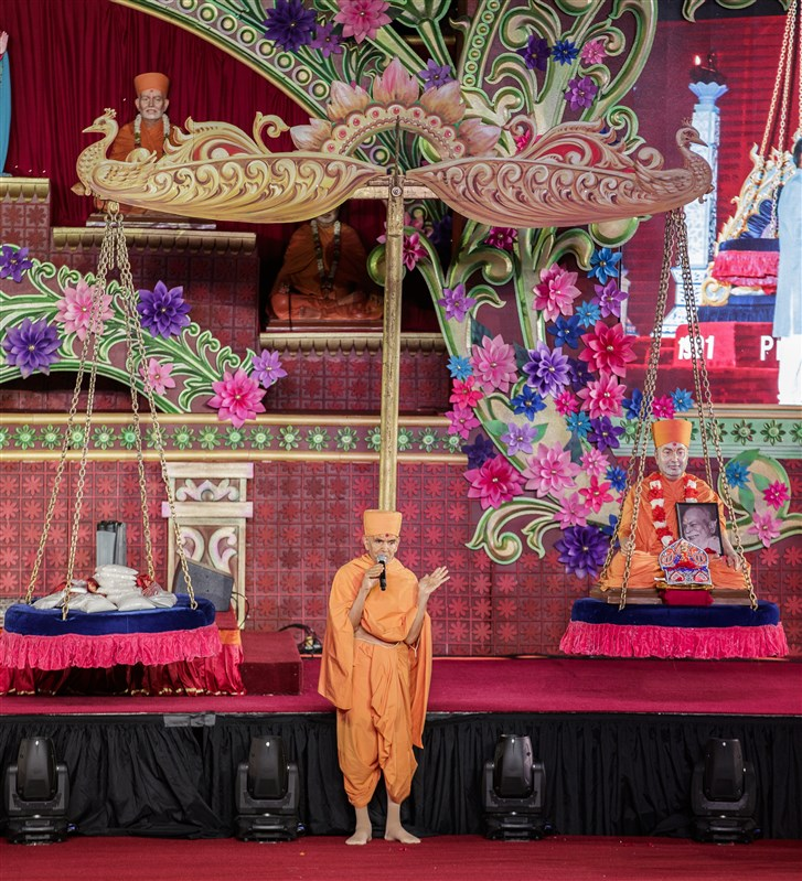 Swamishri addresses the assembly. Seen behind is the tula used during Pramukh Swami Maharaj's Platinum Tula Mahotsav  in Edison, New Jersey on July 20, 1991