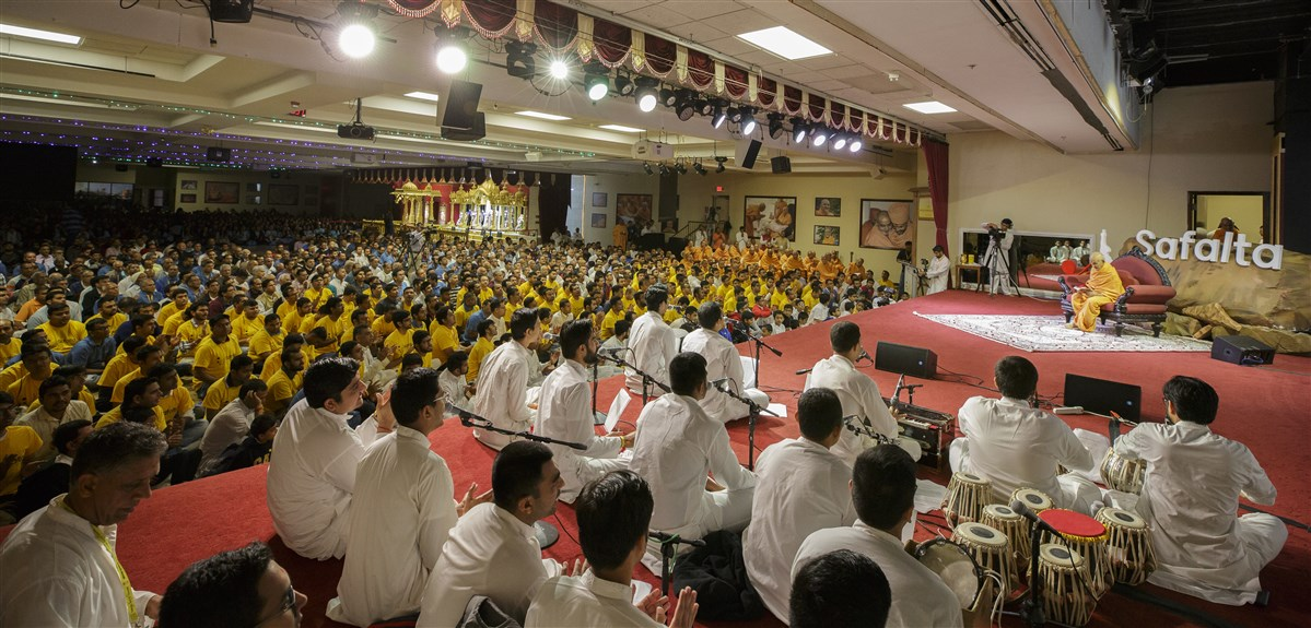 Devotees sing dhun before Swamishri during puja