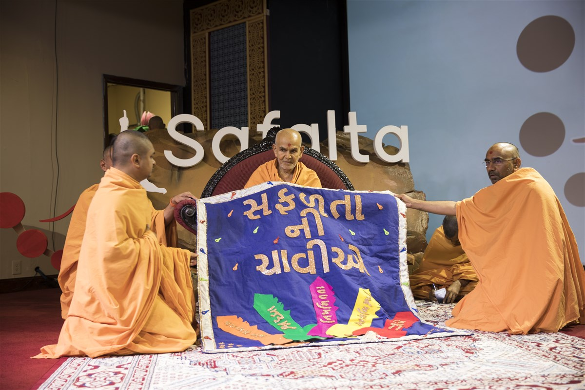 Swamis honor Swamishri with a decorative shawl