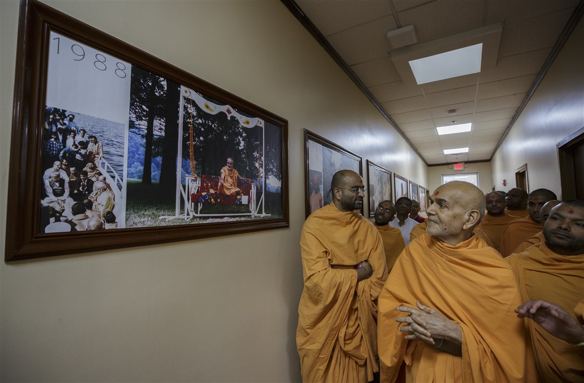 Swamishri engrossed in viewing a photo of Brahmaswarup Pramukh Swami Maharaj from 1988