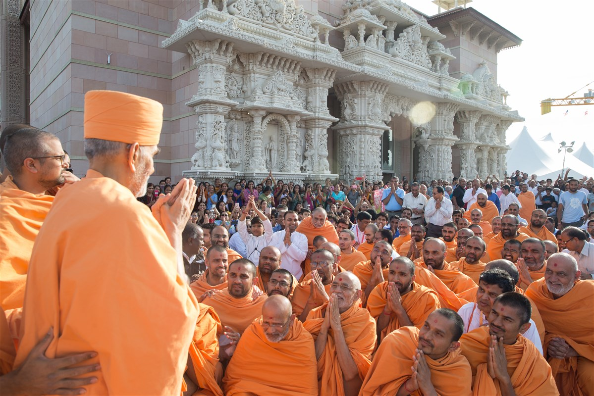 Swamishri greets Swamis and devotees with folded hands