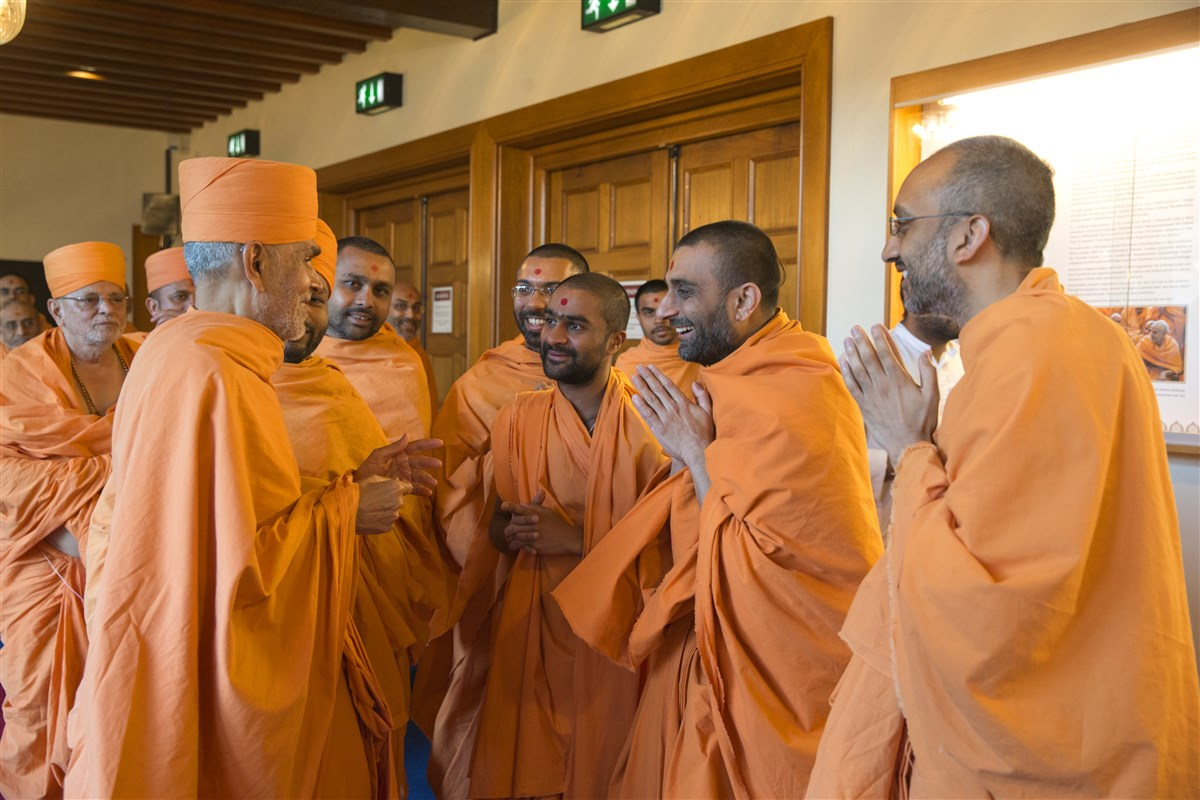 Swamishri warmly greets swamis upon arriving at the Mandir