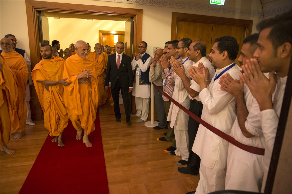 Swamishri greets volunteers as he enters the Haveli assembly hall