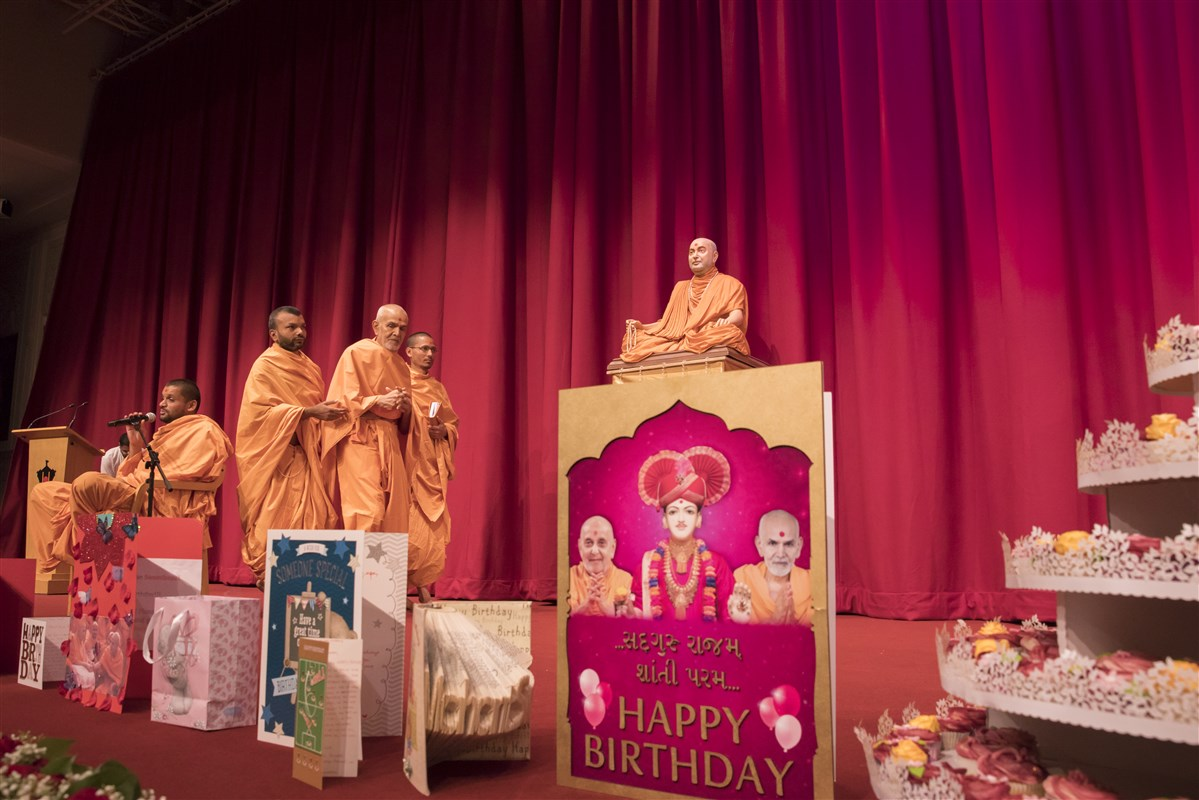 Swamishri arrives in the main hall, which is decorated with a variety of devotional birthday cards and cakes