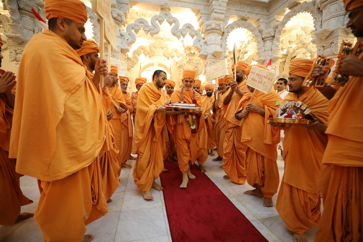 Swamishri begins a ceremonial procession of the <i>Swaminarayan-Siddhant-Sudha</i> vaad-granth from the upper sanctum...