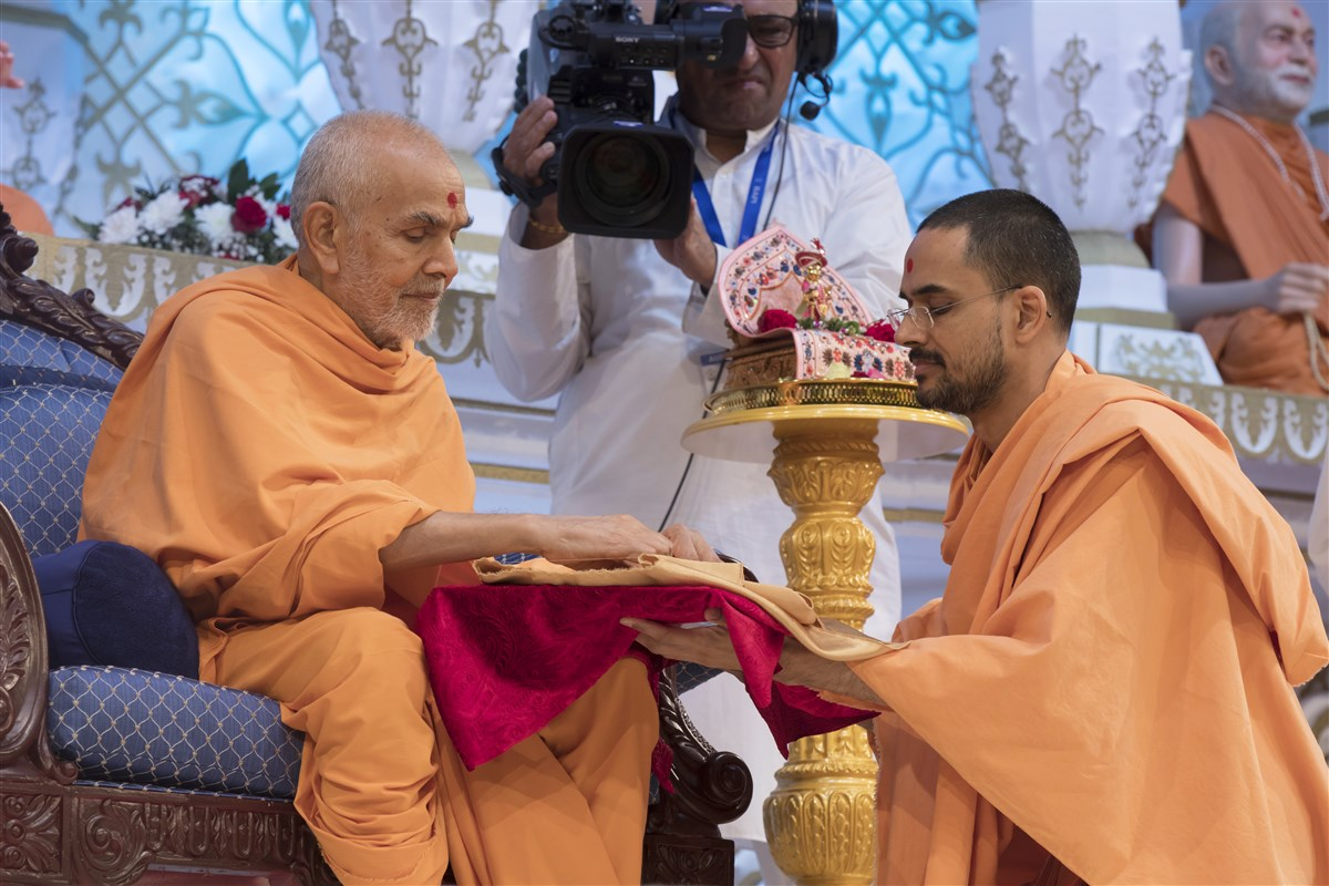 Paramtattvadas Swami offers the new book to Swamishri <i>An Introduction to Swaminarayan Hindu Theology</i>