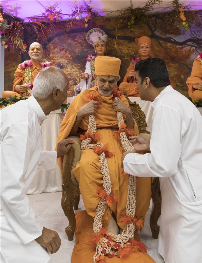 Volunteers warmly greeted Swamishri in the assembly with a decorative garland