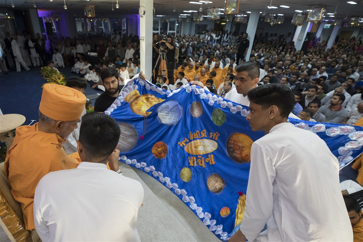 Youths greeted Swamishri with a decorative shawl