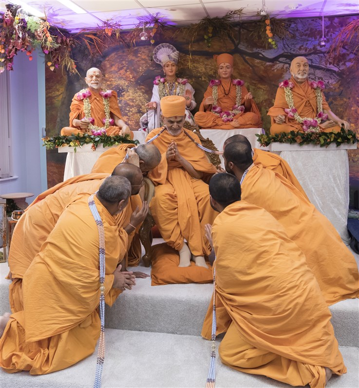 Swamis formerly from South London offered a decorative garland to Swamishri