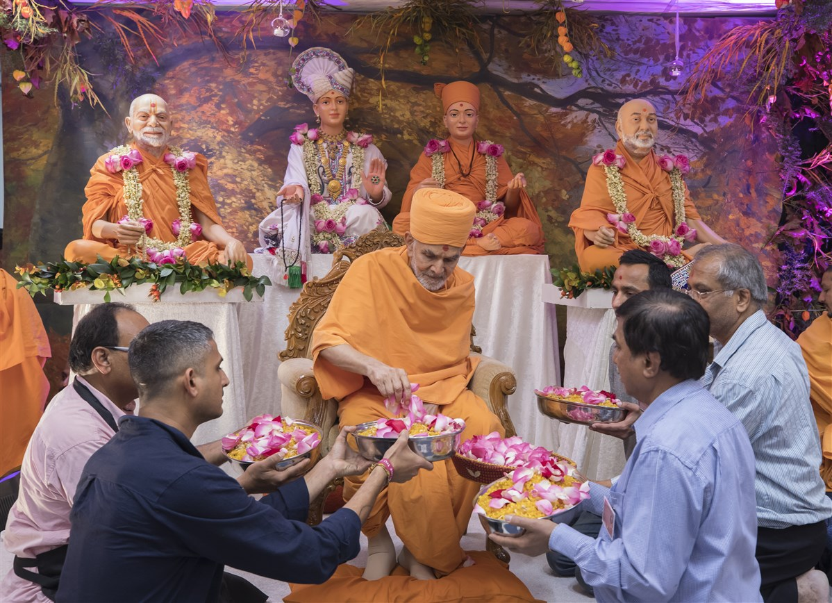 Swamishri sprinkled flower petals on Indian sweets, for sharing with the devotees as prasad