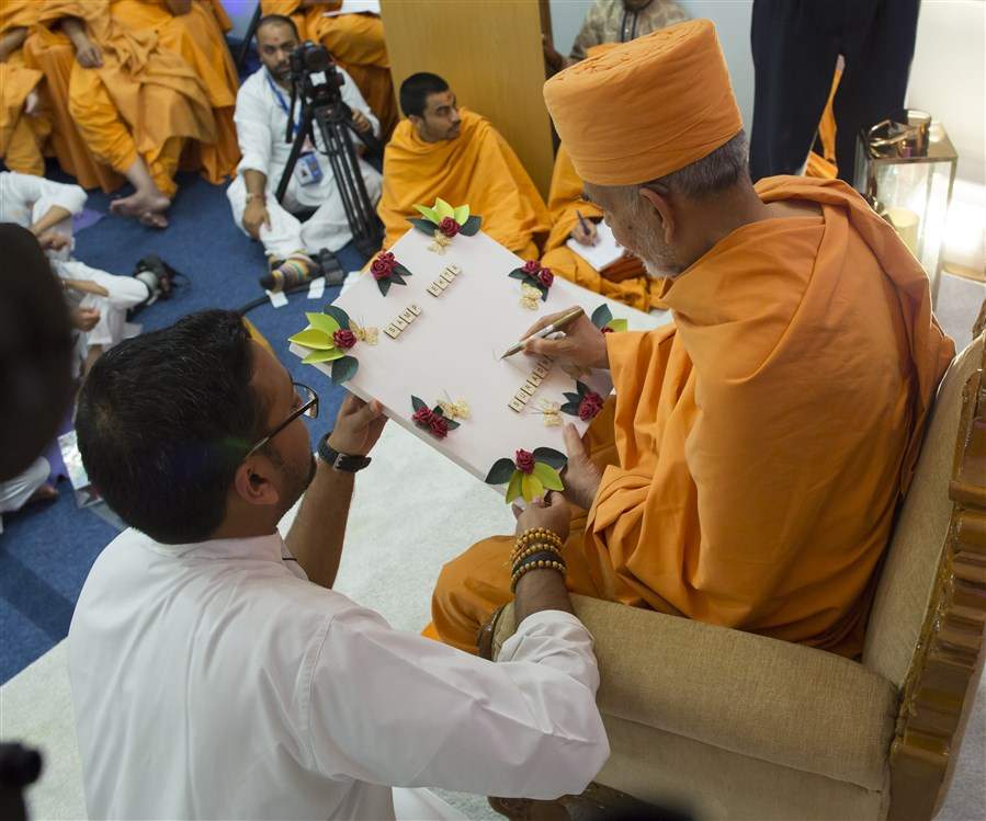 Swamishri signed a decorative card...
