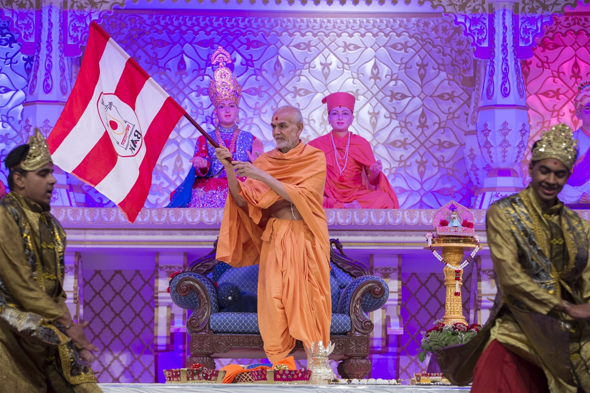 Swamishri waves the BAPS flag in participation of the dance