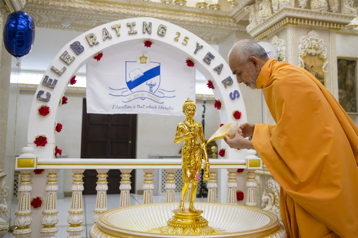 Param Pujya Mahant Swami Maharaj performs the abhishek of Shri Nilkanth Varni, on the 25th anniversary of The Swaminarayan School in London