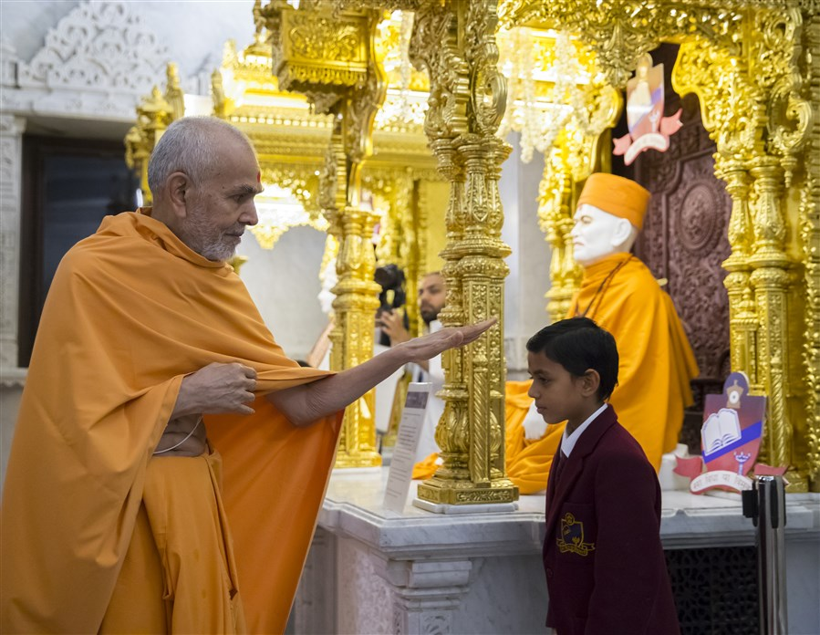 Swamishri blesses a young pupil of The Swaminarayan School