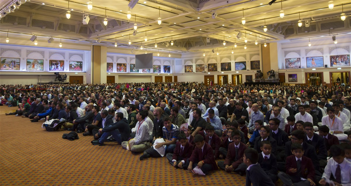 Devotees and school pupils enjoy Swamishri's morning puja