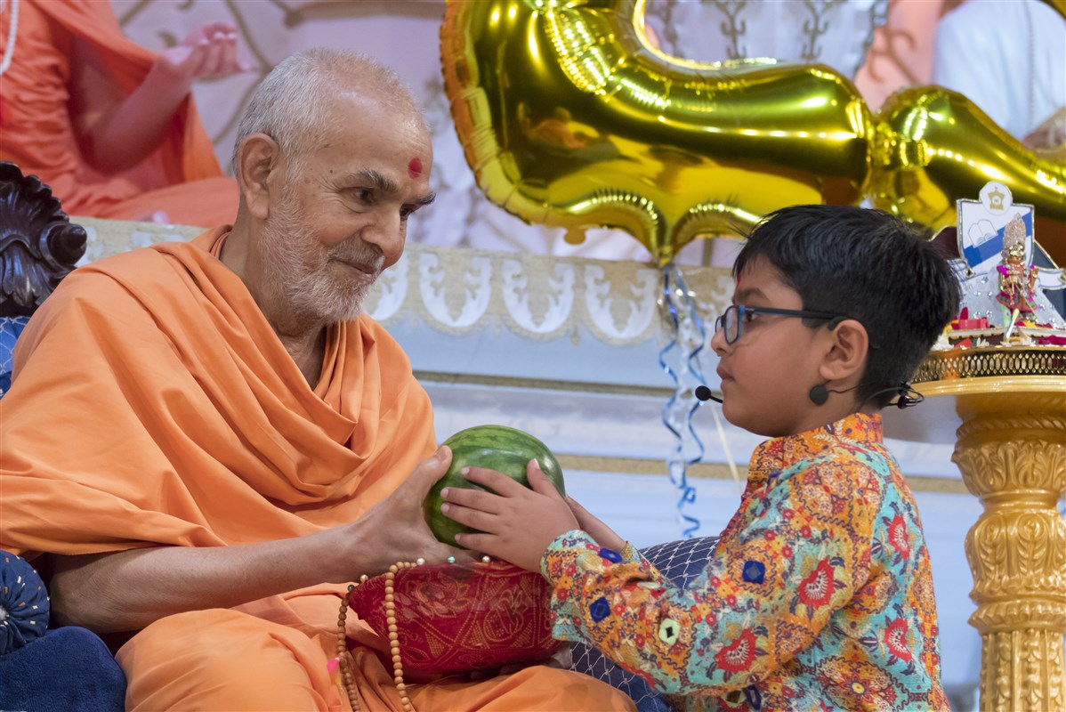 Swamishri engages with a young pupil as a part of his skit