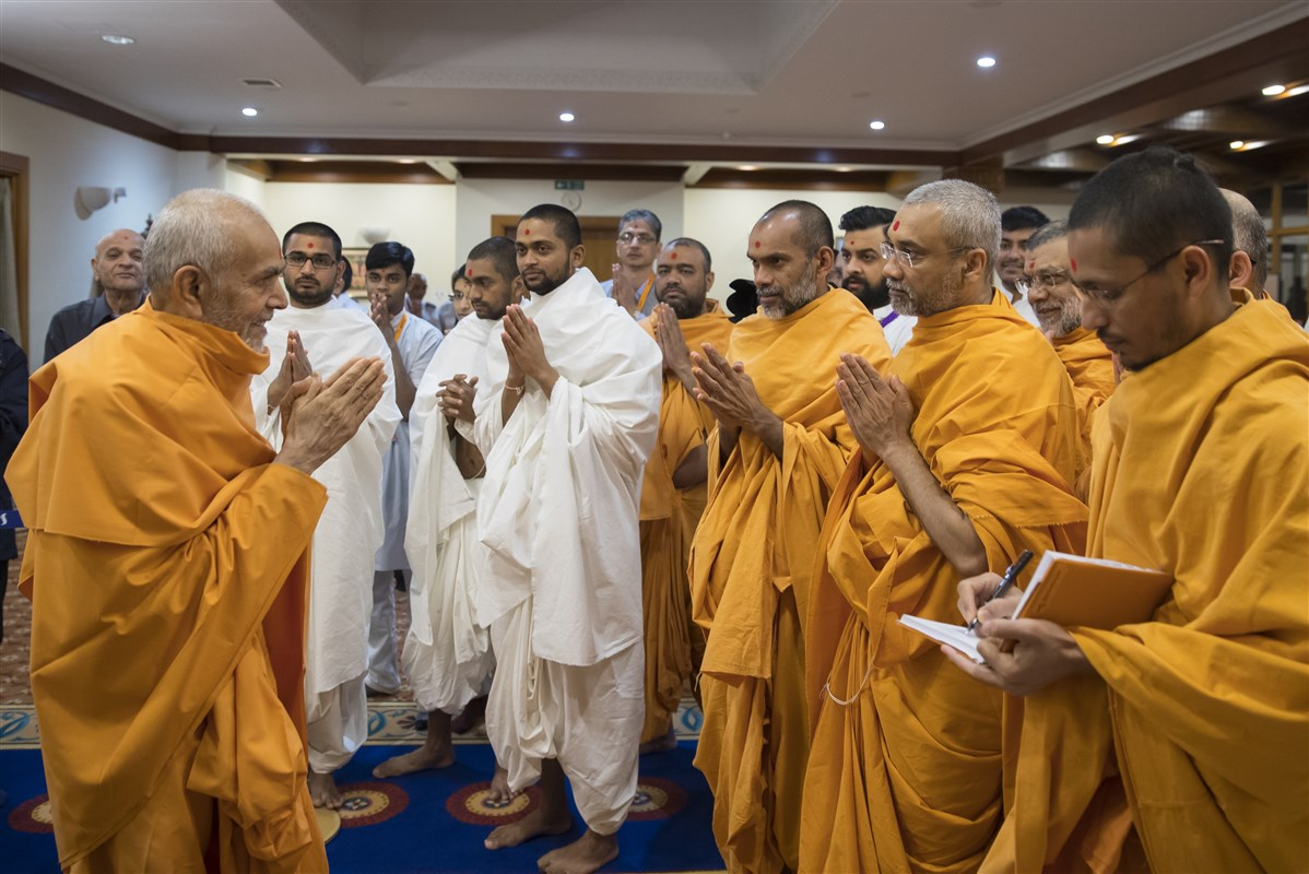 Param Pujya Mahant Swami Maharaj greets swamis with folded hands on his way to darshan