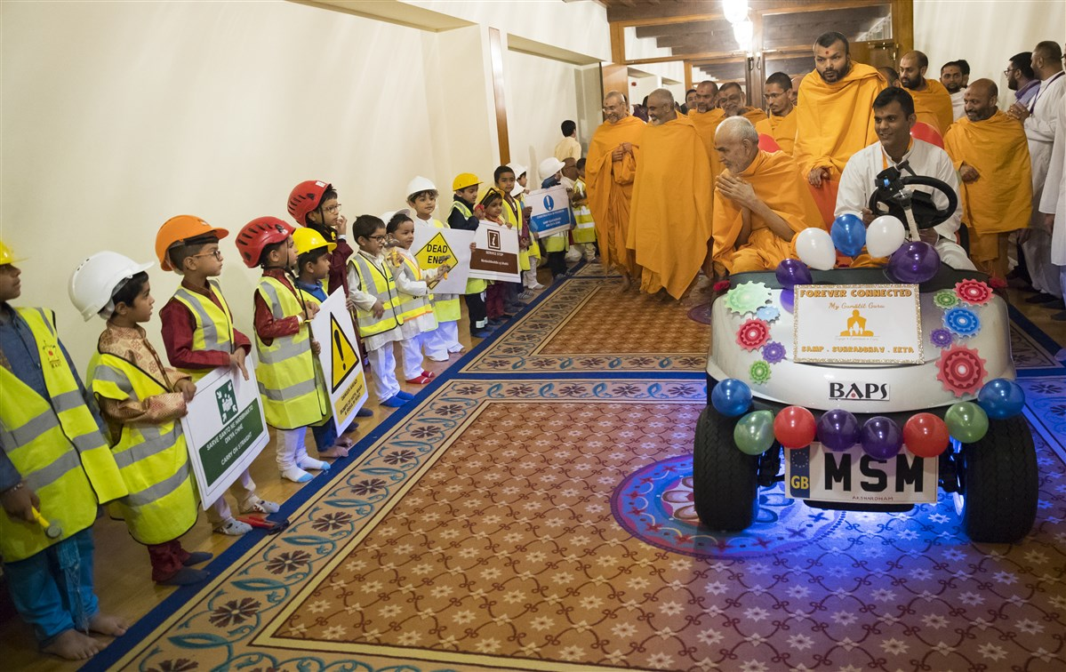 Children dressed as construction workers greet Swamishri with inspiring messages