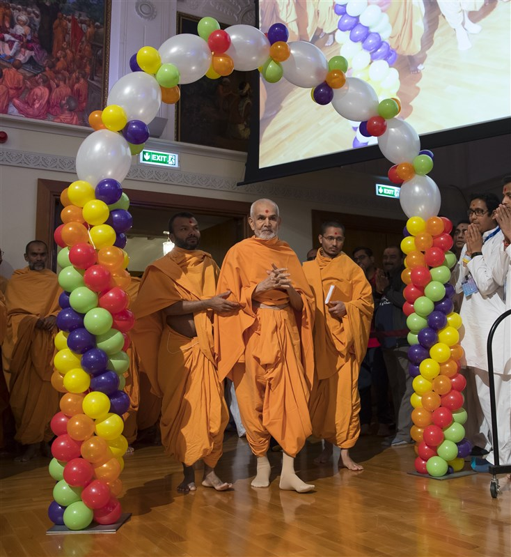 Swamishri arrives in the hall through a decorated arch of balloons