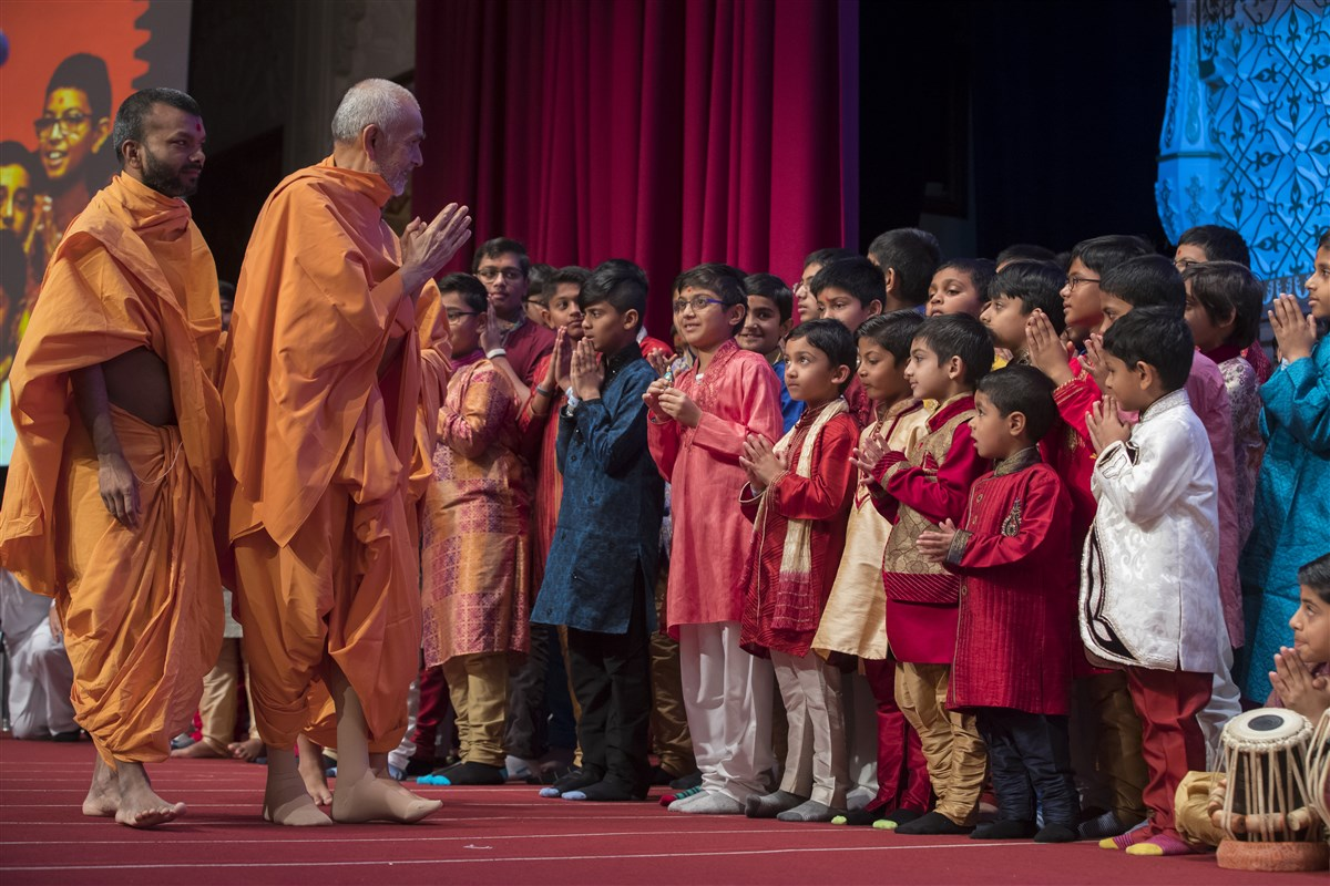 A choir of children greets Swamishri on stage