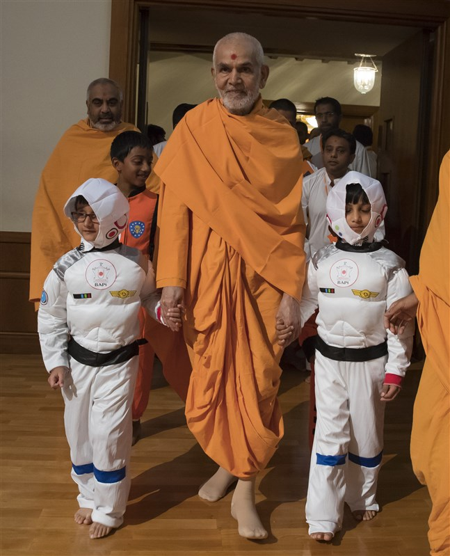 Swamishri arrives in the mid-morning session accompanied by two 'astronauts'