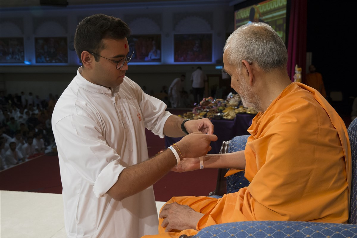 A kishore enrols Swamishri into the Kishore-Kishori Din with a wristband