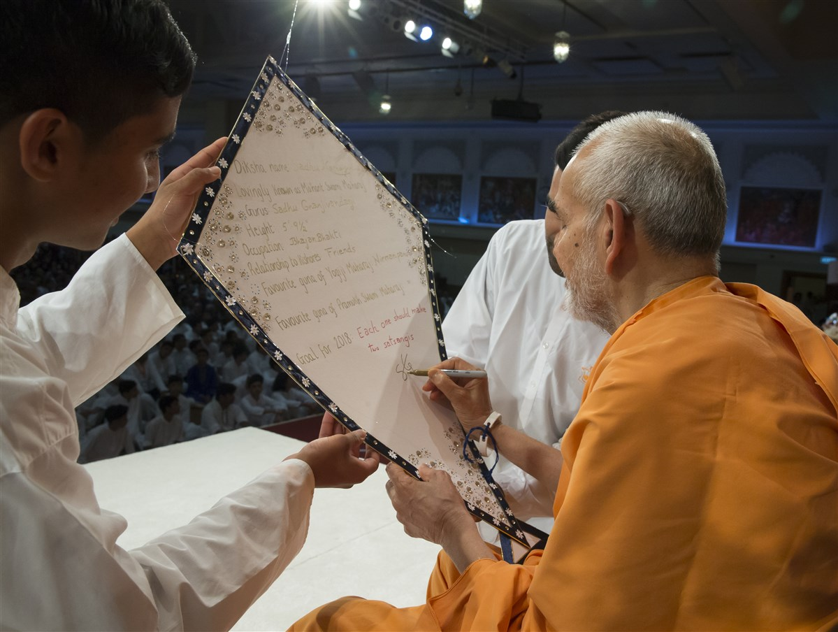 Swamishri signs a kite with his introduction, in preparation for the next session on 'Parichay'