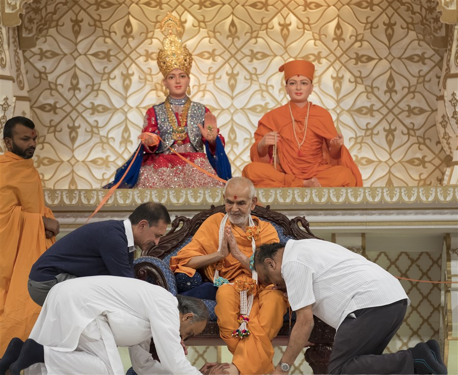 Senior volunteers honour Swamishri with a decorative garland