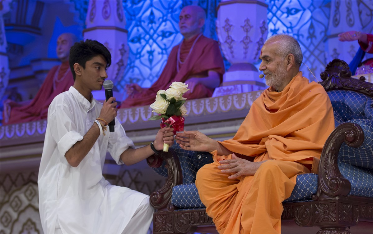A kishore presents a bouquet of flowers to Swamishri, as he had done to Pramukh Swami Maharaj as a child