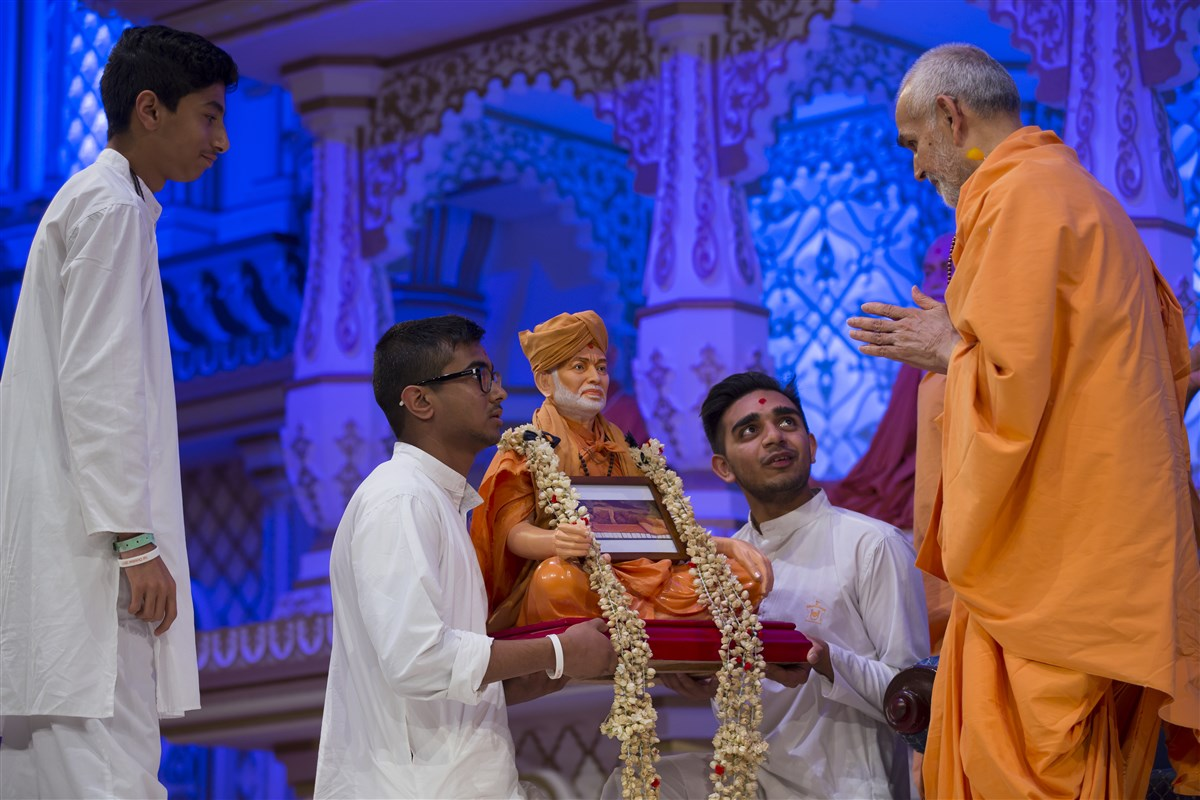 Swamishri offers a fresh flower garland to the murti of Shastriji Maharaj